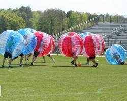 People, in bubbles, playing soccer: Bubble Soccer
